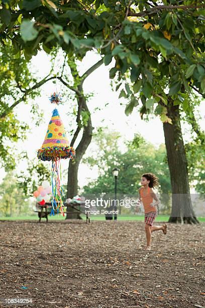 Girl at birthday party running past pinata