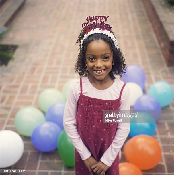 Girl (8-10) at birthday party, wearing party hat, portrait