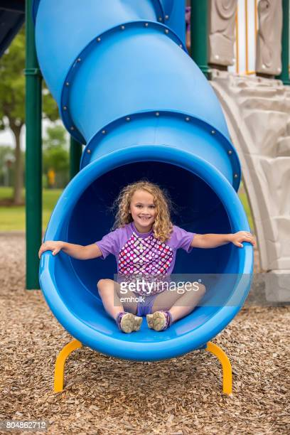 Girl At Bottom Of Blue Tube Slide at Playground