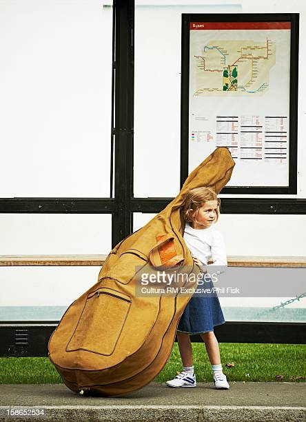 Girl at bus stop with cello case