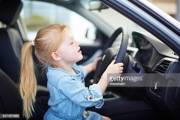 Girl at car dealer inside car steering