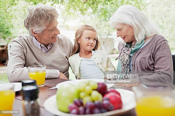girl (6-7 years) at garden table with grandparents - 55 59 years stock pictures, royalty-free photos & images
