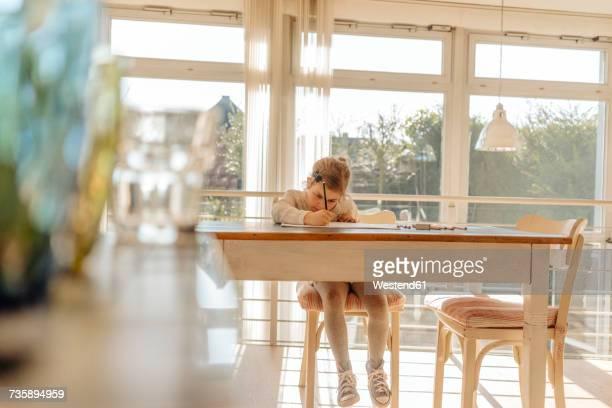 Girl at home drawing at table