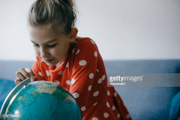 girl at home looking at globe - one world stock pictures, royalty-free photos & images