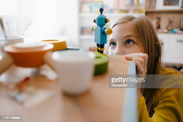 girl at home looking at toy robot - differential focus stock pictures, royalty-free photos & images