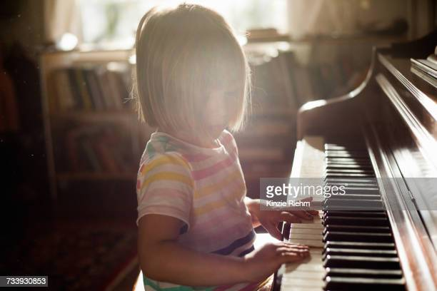 Girl at home playing old piano