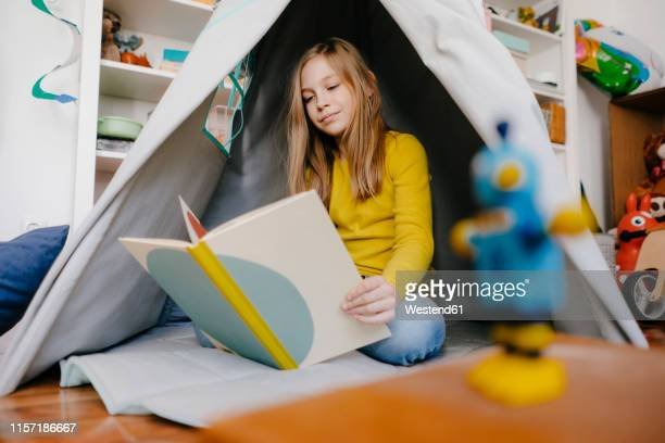 girl at home reading book in children's room - teepee stock pictures, royalty-free photos & images