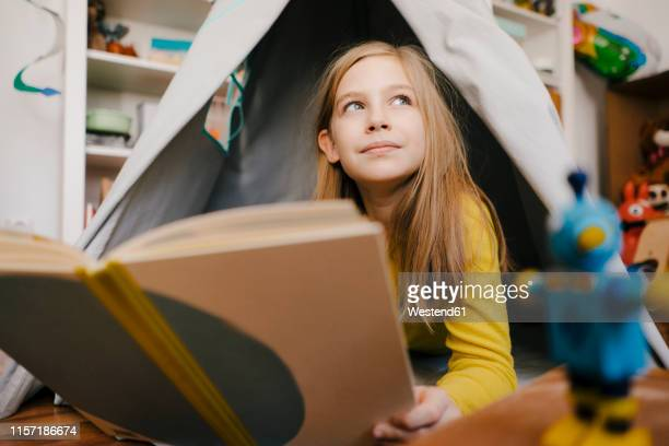 girl at home reading book in children's room - nur kinder stock-fotos und bilder