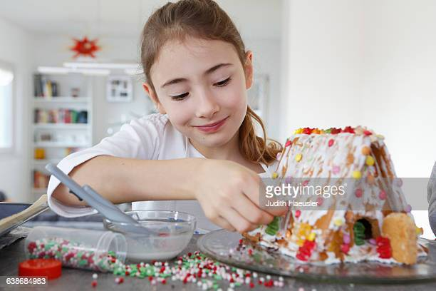 Girl at kitchen counter decorating ginger bread house smiling