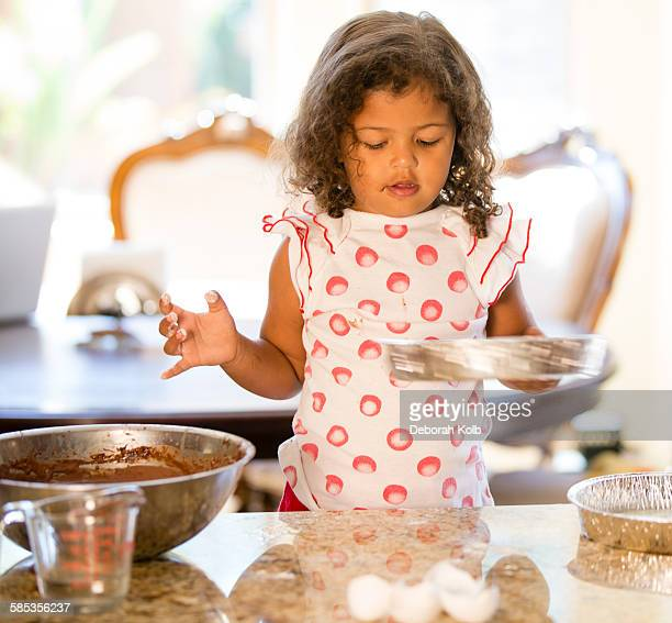 Girl at kitchen counter holding cake tin looking down