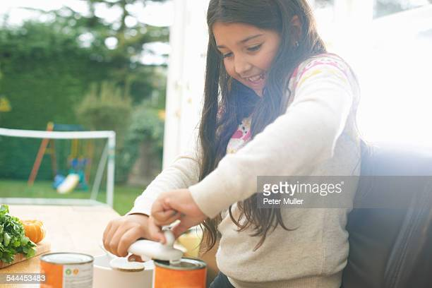 Girl at kitchen table opening can of tomato soup