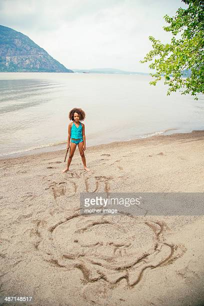 Girl at lake drawing in sand