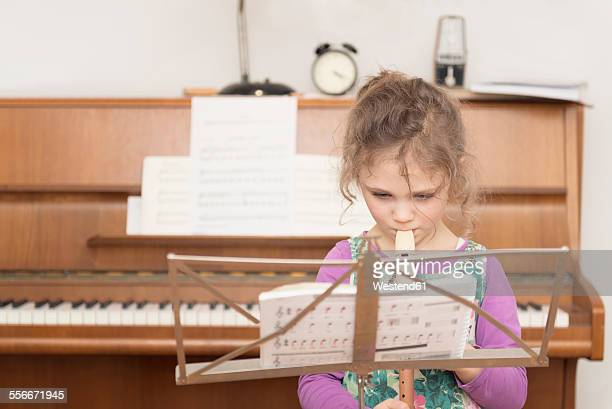 Girl at music stand playing recorder