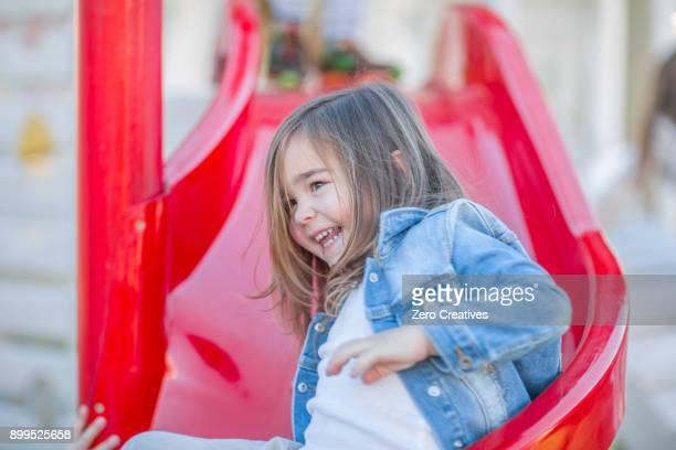Girl at preschool, sliding down slide in garden