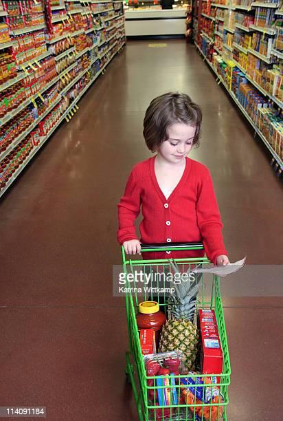 Girl at pushing mini grocery cart.