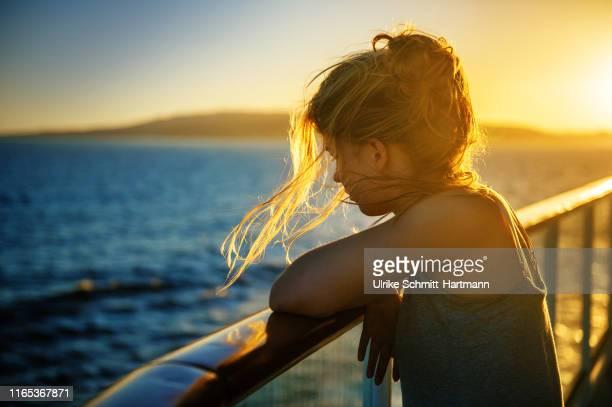 girl at railing at sunset - kriegsschiff stock-fotos und bilder