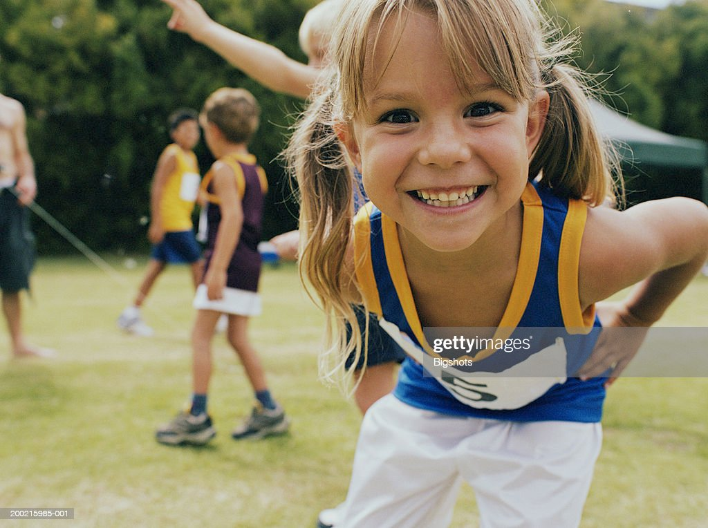 Girl (5-7) at school sports day, smiling, portrait, close-up : Foto de stock