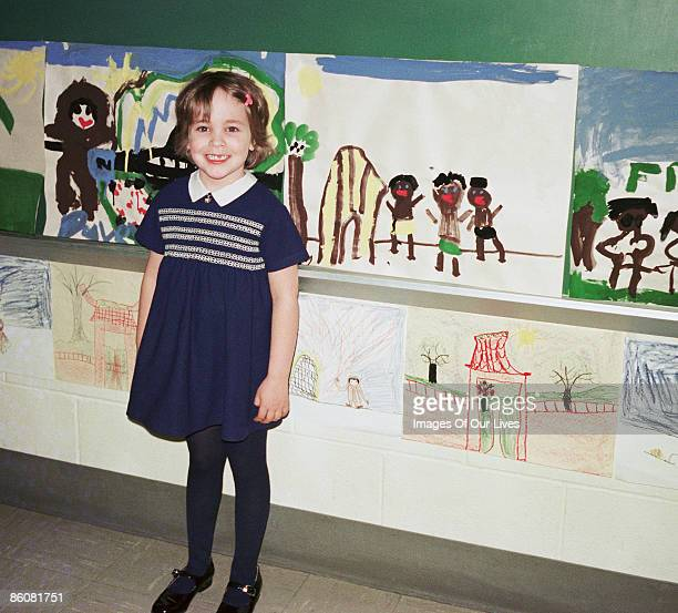 Girl at school standing by wall of paintings