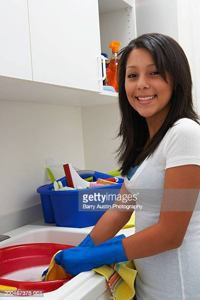 girl (13-15) at sink in laundry room, smiling, portrait - たらい ストックフォトと画像