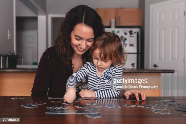 Girl at table doing jigsaw puzzle with mother