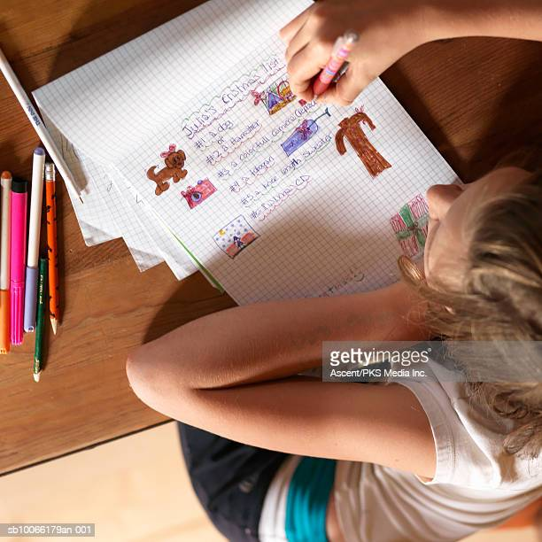 Girl (12-13) at table writing on book, overhead view