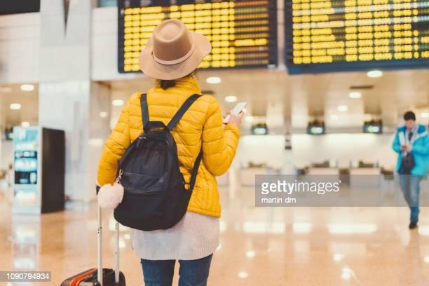 mädchen am flughafen überprüft die ankunft abfahrtstafel - südostengland stock-fotos und bilder