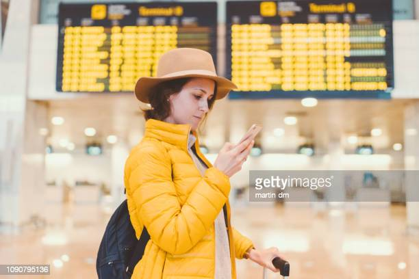 girl at the airport checking the arrival departure board - heathrow stock pictures, royalty-free photos & images