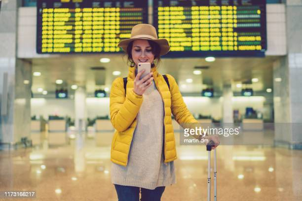 girl at the airport checking the arrival departure board - airport stock pictures, royalty-free photos & images