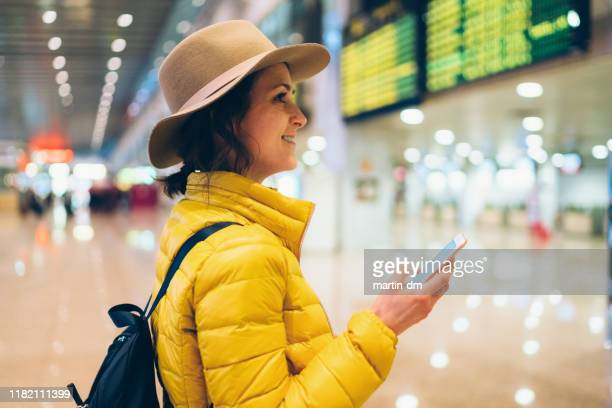 girl at the airport checking the arrival departure board - latium stock pictures, royalty-free photos & images