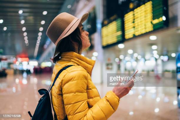girl at the airport checking the arrival departure board - leaving stock pictures, royalty-free photos & images
