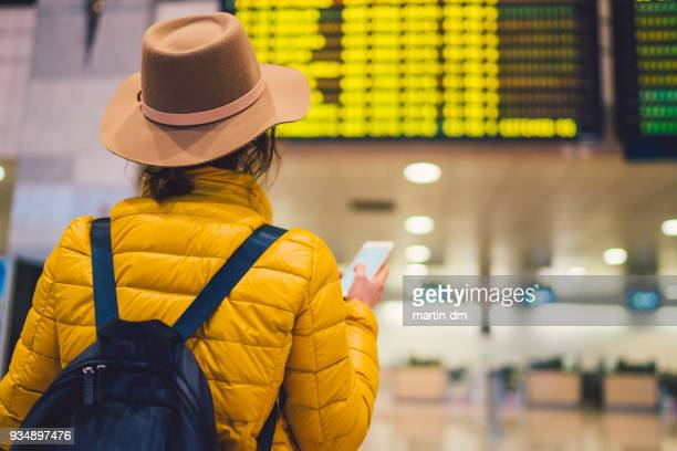 girl at the airport checking the arrival departure board - charles de gaulle airport stock photos and pictures