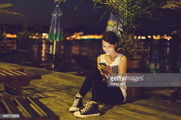 Girl at the beach by night using smartphone
