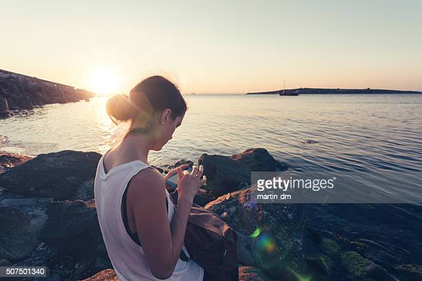 Girl at the beach texting on sunset