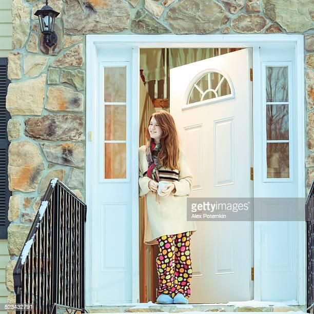 Mädchen im Türrahmen vor contry house im winter