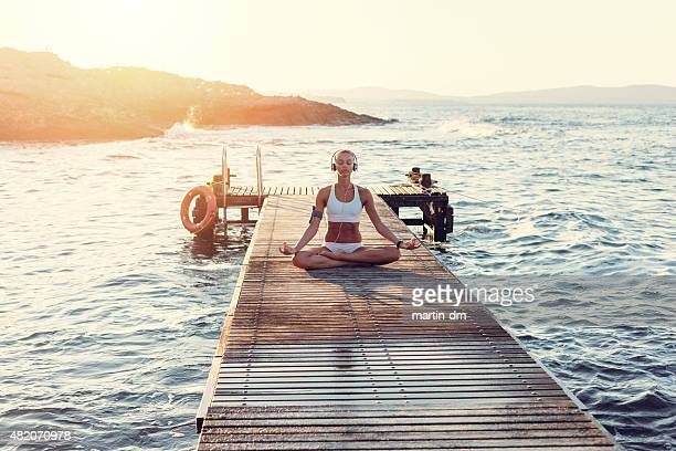 Girl at the jetty meditating on sunset