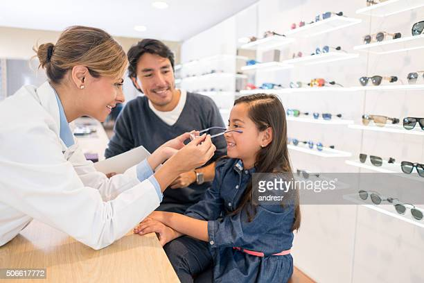 girl at the optician's shop trying new glasses - optometry stock pictures, royalty-free photos & images