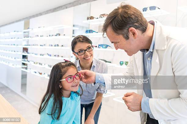 Girl at the optician's shop trying new glasses
