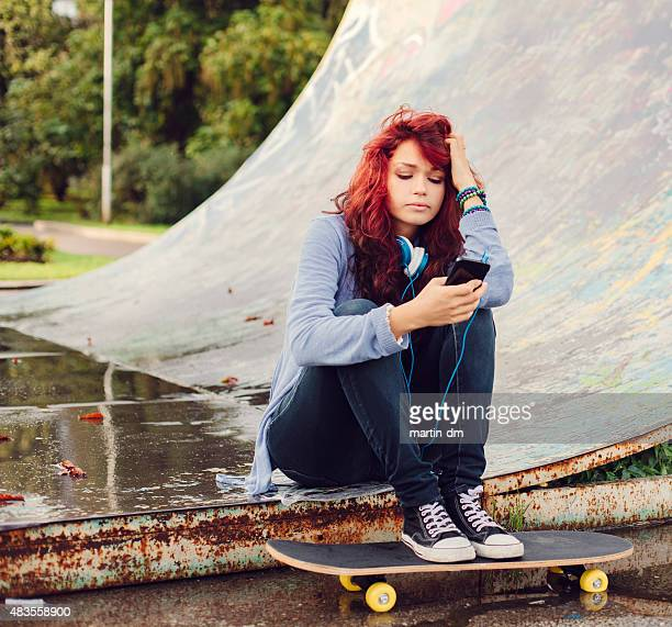 Girl at the skate ramp texting on smartphone