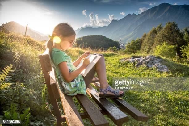 Mädchen an den Sonnenuntergang sitzen auf Bank zeichnen den Blick auf die Berge