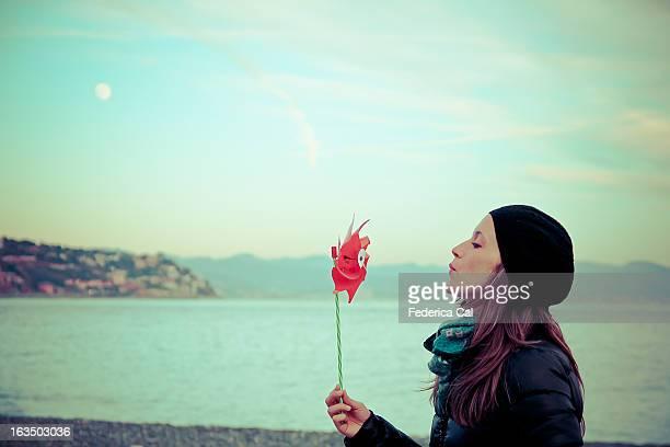 Girl at winter seaside, blowing red pinwheel