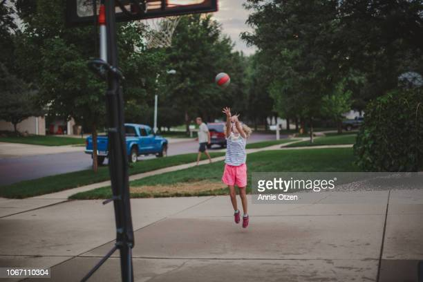 girl attempting to throw a basketball through a hoop - shooting baskets stock pictures, royalty-free photos & images