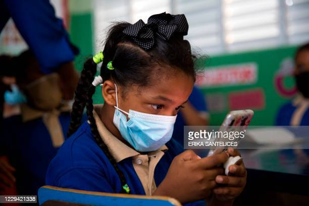 Girl attends a class for children of teachers at the Eulalio Arias School in Santo Domingo, on November 2, 2020 during the first day of school in the...
