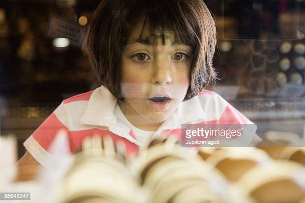 Girl awed by chocolate bonbons in glass case