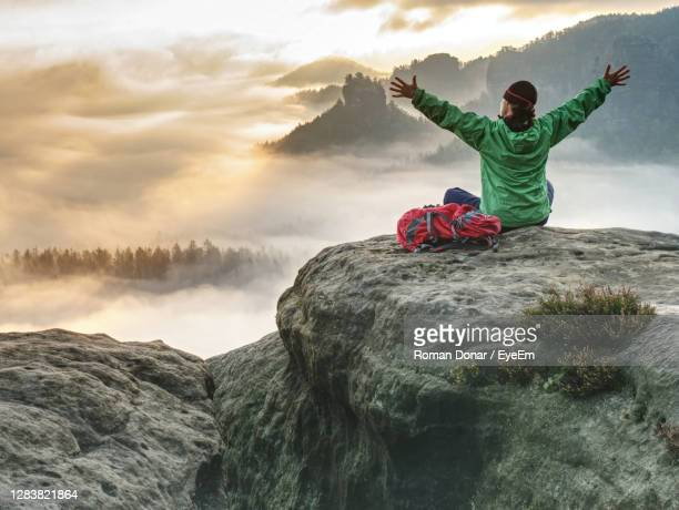 girl backpacker sitting on top of the mountain and enjoying new born of the day. fall season hike. - top fotografías e imágenes de stock