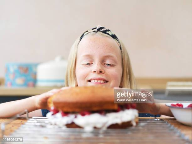girl baking a cake, pressing top cake sponge at kitchen table - cake stock pictures, royalty-free photos & images