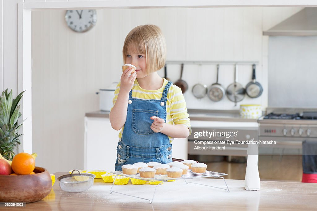 Girl baking cupcakes in kitchen : Stock Photo