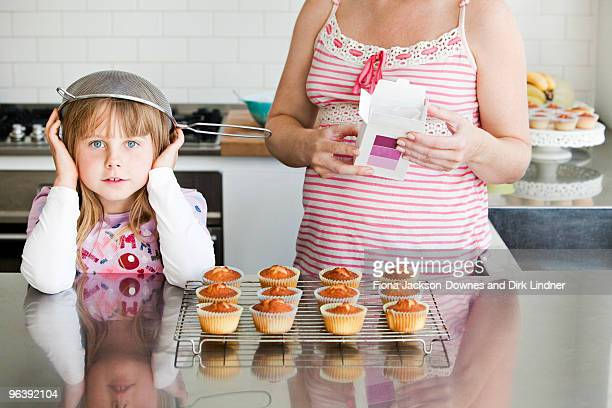 Girl baking with sieve on her head