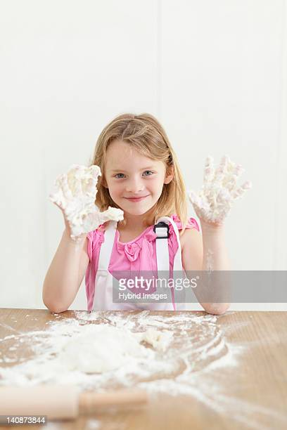 Girl baking with sticky hands in kitchen