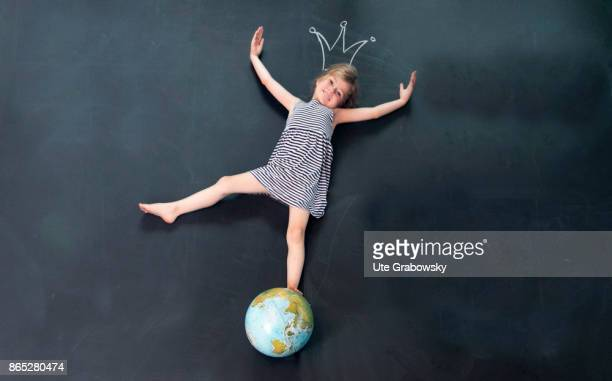 A girl balances on a globe in front of a blackboard Above her head a crown is painted with chalk on the blackboard on August 08 2017 in Sankt...