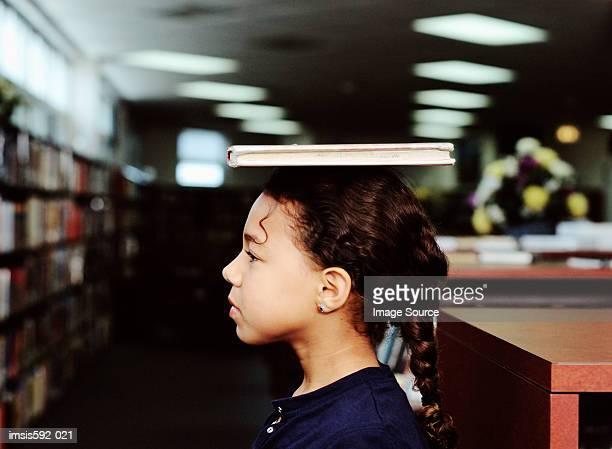 Mädchen Ausgleich ein Buch auf dem Kopf